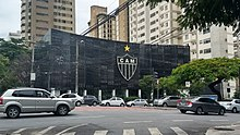 A street filled with cars in front of a metal façade in black, with a large football club badge.