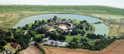 Aerial view of the fort showing the fort itself at the centre, surrounded on three sides by a moat. An area of marshy grassland bordered by the river is visible in front of the fort. Behind it are trees, fields, a car park and a church.