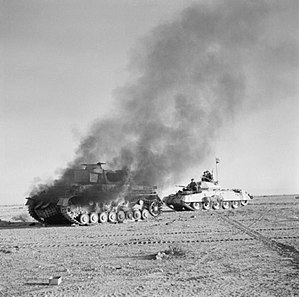 Operation Crusader - A Crusader Mk.I passes a burning German Panzer IV, 27 November 1941.