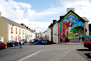 "Cushendall village with <a href=""http://search.lycos.com/web/?_z=0&q=%22hurling%22"">hurling</a> mural"