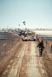 A column of M-113 APCs and other military vehicles of the Royal Saudi Land Force travels along a channel cleared of mines during Operation Desert Storm, Kuwait, 1 March 1991.