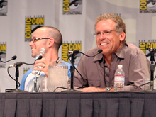 Two men seated in front of a table with microphones. The San Diego Comic Con logo can be seen in a panel behind them.