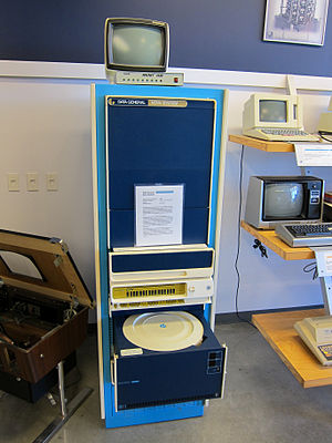 Data General Nova - A Nova system (beige and yellow, center bottom) and a cartridge hard disk system (opened, below Nova) in a mostly empty rack mount.