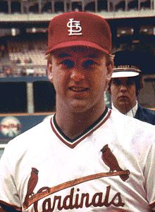 "A man in a white pullover baseball jersey with ""Cardinals"" across the chest in red script, accompanied by a baseball bat and two male cardinal birds, and a red baseball cap with a white interlocking ""StL"""
