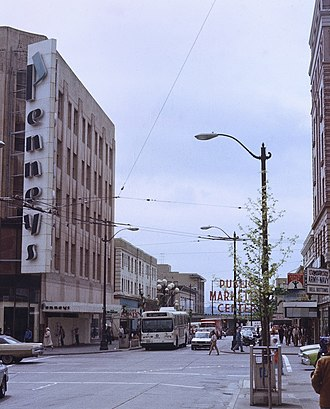 J. C. Penney - Former Downtown Seattle store in 1982, with signage from the period when the chain was branded as Penneys and used a more stylized font in its logo. Pike Place Market is in the background.
