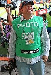Carey sonriendo ampliamente, sin sus lentes habituales y con ropa informal con una camiseta verde de entrada al concurso.  Él sostiene una cámara con una lente larga.