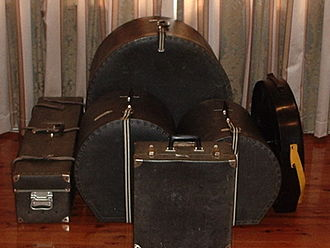 Traps case - A five-piece drum kit in hard cases, with the traps case at the left. Note the trunk handles to help bear the weight, which are not needed on any of the other cases.