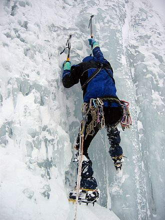 Climbing - An ice climber using ice axes and crampons.