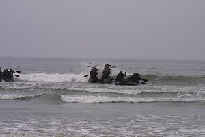 United States Marine Corps Force Reconnaissance - A platoon of Force Recon team operators paddle their Combat Rubber Reconnaissance Craft (CRRC) against the surf out to sea, a skill that they learned since their days in the Basic Recon Course.