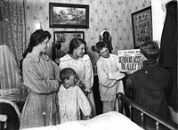Family reads newspaper on Armistice Day.jpg