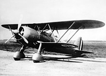 A black and white photograph of a single-propeller biplane on the ground