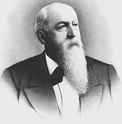 Formal portrait, head and shoulders, of serious-looking man of about 60 dressed in a dark suit jacket and white shirt. He is bald in front, and his remaining hair is white. He has a long, carefully combed white beard.