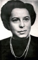 Woman with short, dark hair and dark clothing, accented with a necklace