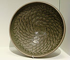 A grey-green shallow bowl with a painted decoration on the inside consisting of dozens of small petals moving outward from the center of the dish in a spiral pattern.