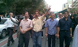 "Heshmat Tabarzadi - ""Heshmatollah Tabarzadi at the rally with people,for to protect elections result in Iran , Tabarzadi raised his finger to signal victory in this photo ,Tehran ,September 2009"