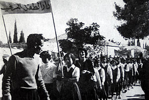 "Hind al-Husseini - Hind al-Husseini demonstrating with schoolgirls, Jerusalem, (?). The banner reads: ""Dar al-Tifl al-Arabi""."