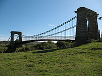 Suspension bridge with stonework arches either end, partly silhouetted against clear blue sky, green field in foreground
