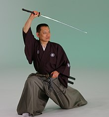 A man in baggy robes and split pants kneels on one knee and holds a Japanese sword above his head.