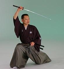 Seorang pria dengan jubah longgar dan celana perpecahan berlutut dengan satu kaki dan memegang pedang Jepang di atas kepalanya.