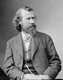A finely detailed monochrome photograph portrait of a bearded and mustachioed man in his 30s or 40s, shown from the waist up, wearing a jacket and vest over a white shirt with its collar closed by a cravat secured by a jeweled finger ring, a multi-corded watch fob hanging from a vest button, decorated by another ring, the man's hands together in his lap, his body leaning to the left and the head turned to the right, his dark hair full and long in the back, long but thin on top, revealing a high forehead