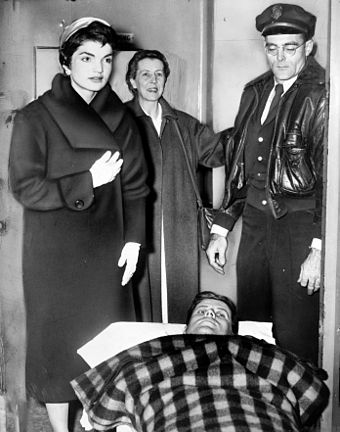 Kennedy lying on a gurney following spinal surgery, accompanied by Jackie, December 1954 John F. Kennedy after spinal surgery cph.3c33052.jpg