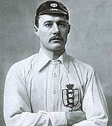A black-and-white upper-body photograph of a man wearing a white shirt and a dark cap. He has a moustache and his arms are folded.