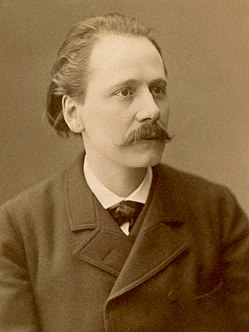 Middle-aged man, receding hair, moustached, looking at camera