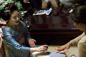 "Geisha - Maiko Tomitsuyu playing the game ""Konpira Fune Fune"" with a female patron"