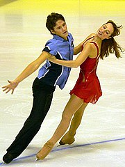 Skaters performing parallel mirror spread eagles. He is on an inside edge and she is on an outside edge.