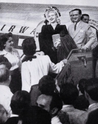 Woman exiting a plane amid crowd