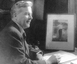 A black and white photograph of a smiling man seated at a desk. He is holding a pen, with a jotter open in front of him and a photograph on the desk.