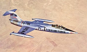 Jet fighter in metallic scheme with T-tail and short wings flying above desert and black constructions