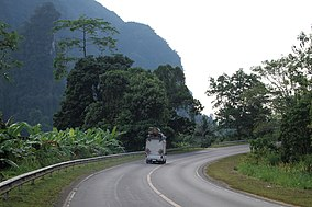 Lonely road through tropical rainforest and karst formations in Surat Thani wilderness, Thailand.jpg
