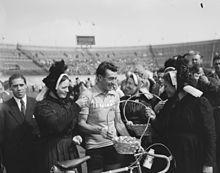 Photographie en noir et blanc d'un cycliste à l'arrivée d'une course, entouré par la foule et trois femmes en costume traditionnel breton.