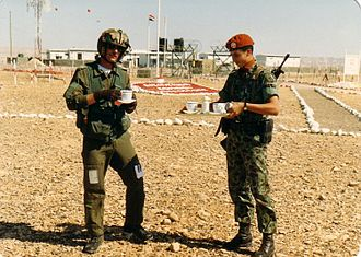 Multinational Force and Observers - A Colombian soldier hosts a Canadian helicopter pilot 1989. The Colombian is wearing the distinctive terracotta-colored beret that is unique to the MFO.