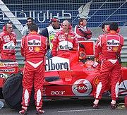 Prominent Marlboro branding on Ferrari F1 car and team at the Bahrain Grand Prix 2006.