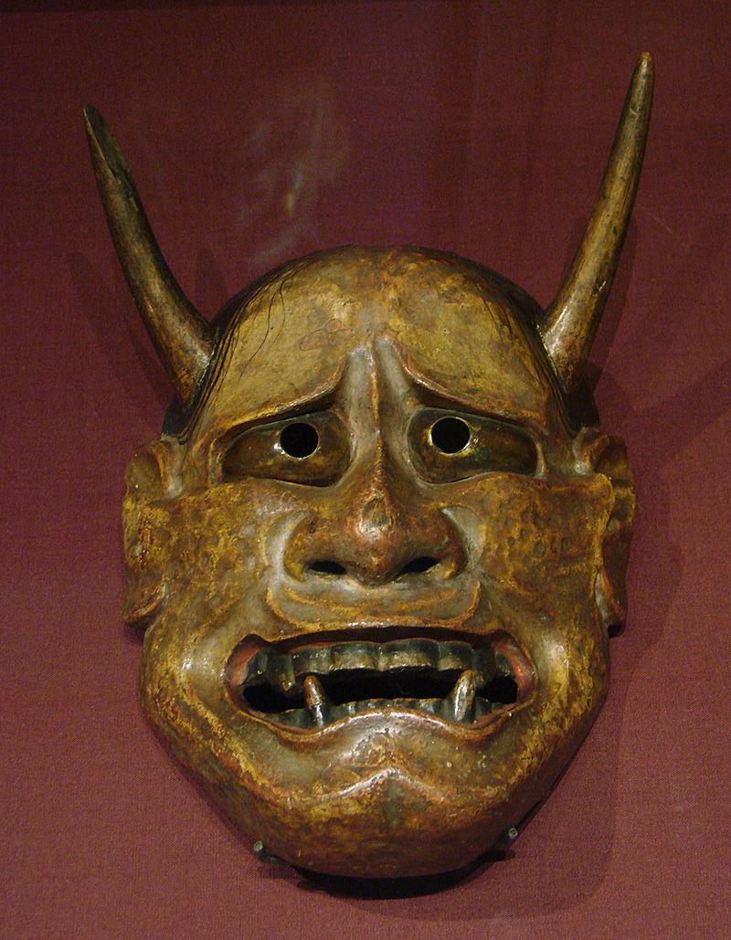 Masque non humain, jaunâtre, avec des cornes, de grandes canines, au regard implorant.