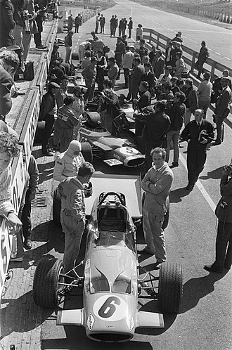Bruce McLaren - McLaren (centre left, white balaclava) prepares to take his seat in his McLaren M7C Formula One car, prior to the 1969 Dutch Grand Prix.