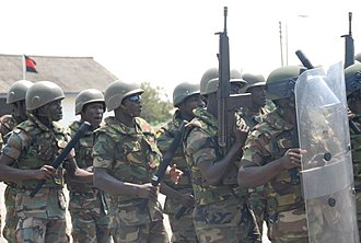 """Ghana Army - Ghanaian combat engineers assemble in a riot control formation known as a """"flying wedge""""."""