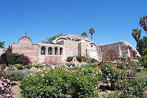 "Catholic missions - Mission San Juan Capistrano in April 2005. At left is the façade of the first adobe church with its added espadaña; behind the campanario or ""bell wall"" is the ""Sacred Garden,"" in what is reputed as the ""Loveliest of the Franciscan Ruins."""