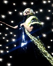 A blond woman wearing a shiny black dress and her hair extended with long braids, stands on a stage. The braids fall on her left arm and continue down. Behind her, a number of twinkling lights are visible and the woman makes a gesture with her right hand.