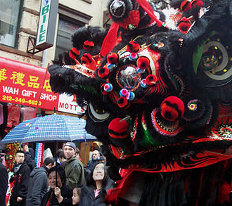 Lion dance - A Cantonese Guan Gong (Kwan Kung) lion ushers in the Chinese New Year in Chinatown, Manhattan, New York City (USA).
