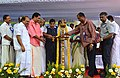 Nitin Gadkari lighting the lamp at the foundation stone laying ceremony for construction of Kollam bypass on NH47, at Kavanadu, Kollam, Kerala. The Chief Minister of Kerala, Shri Oommen Chandy and the State PWD Minister.jpg