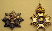 Two jeweled star-burst medallions. One is heavily crusted with carved gold and small gold beads; the other has carved gold, with a central jewel.