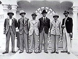 Thirteen men in dark military uniforms standing outside a building