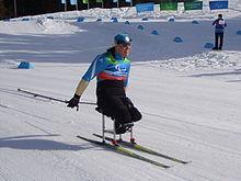 En kvinde, der sidder på sit-ski, skubber hun sig selv med to stænger