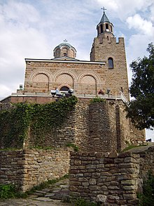 View of a medieval Byzantine-style church's front facade and bell tower slightly from below, with partially destroyed stone walls in the foreground