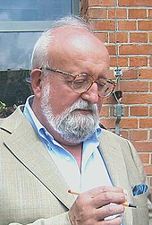 A man with a grey beard: he is wearing glasses and a blue shirt.