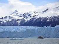 Photograph of a tourist yatch near a glacier wall
