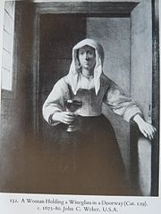 A Woman Holding a Wineglass in a Doorway